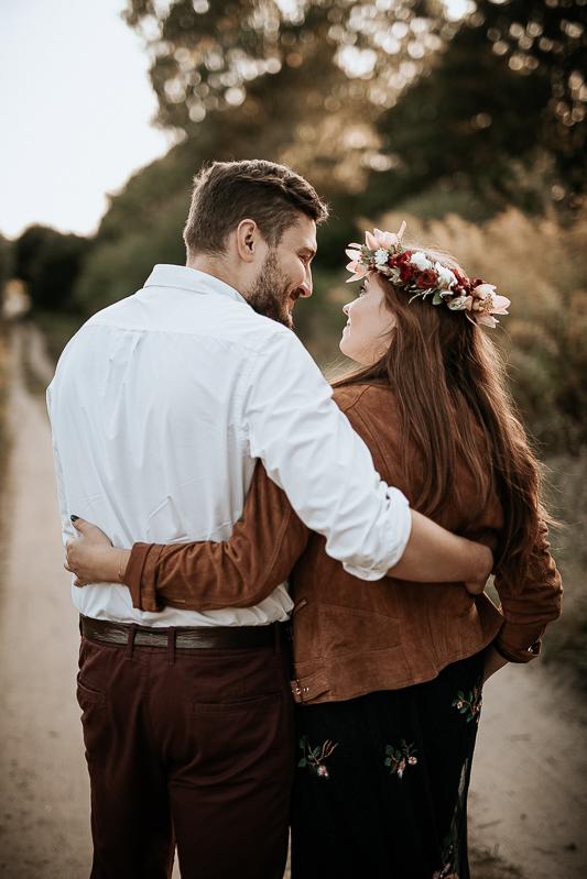 Zakochani stoją na drodze i obejmują się.
