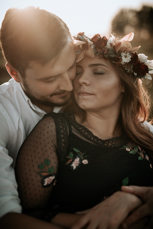 Zakochani trzymają siebie w ramionach i mają zamknięte oczy.