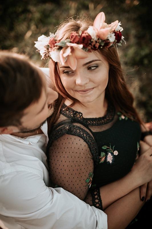 Kobieta patrzy na mężczyznę który trzyma ją w objęciach.