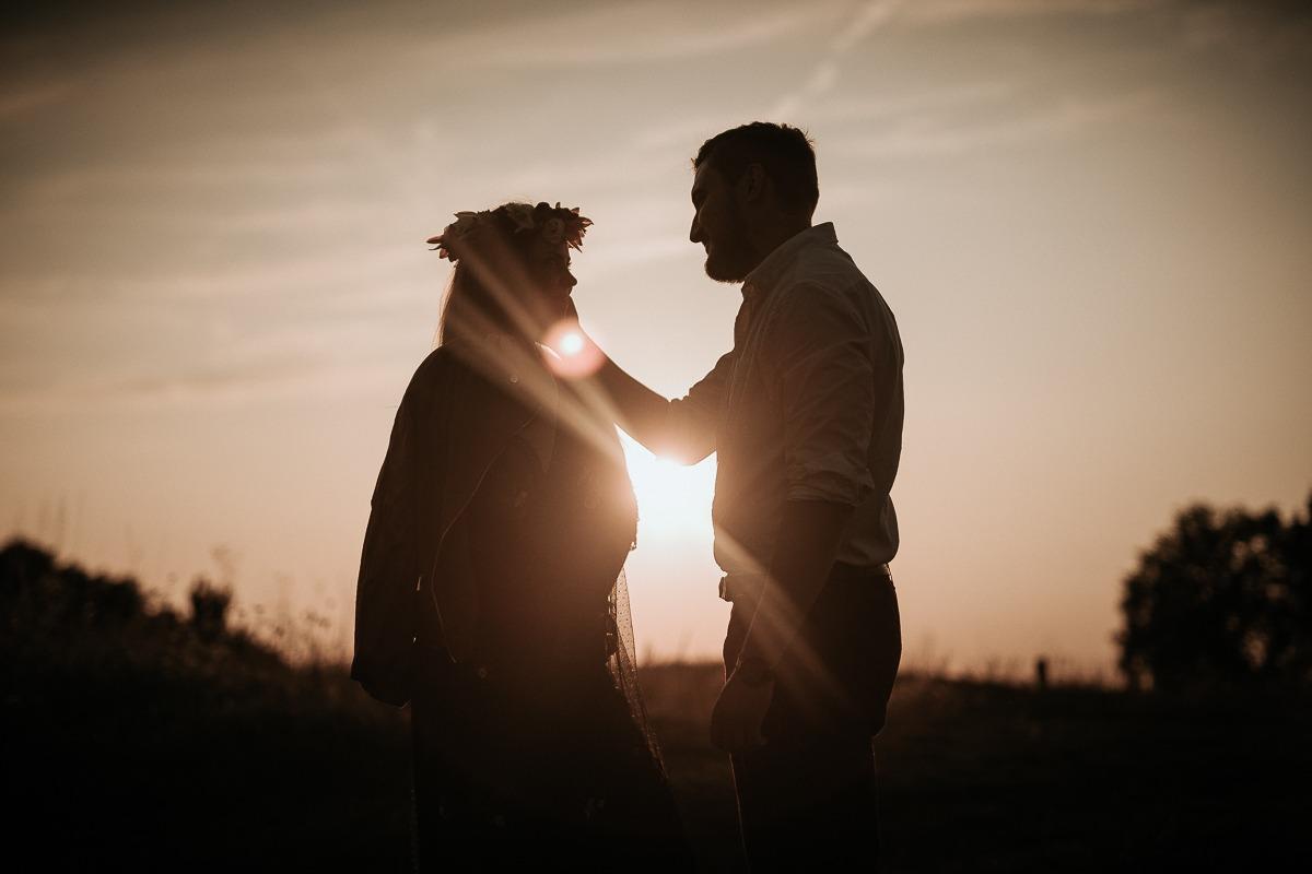 Kontury pary podczas zachodu słońca. Mężczyzna kładzie dłoń na twarzy kobiety.