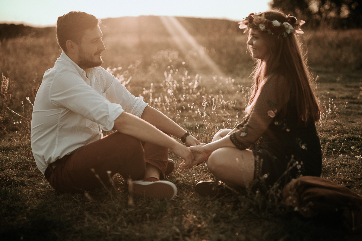 Zakochani siedzą na łące i patrzą sobie w oczy