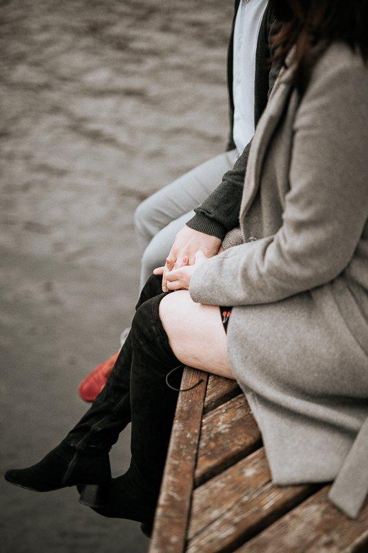 para siedzi na pomoście ze spuszczonymi nogami