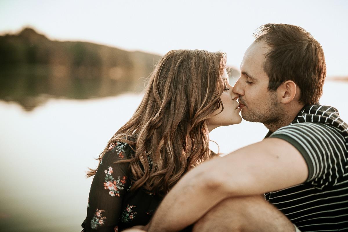 Zakochana para całuje się siedząc nad jeziorem