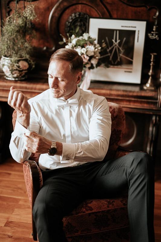 Pan młody siedzi w fotelu i poprawia mankiet białej koszuli