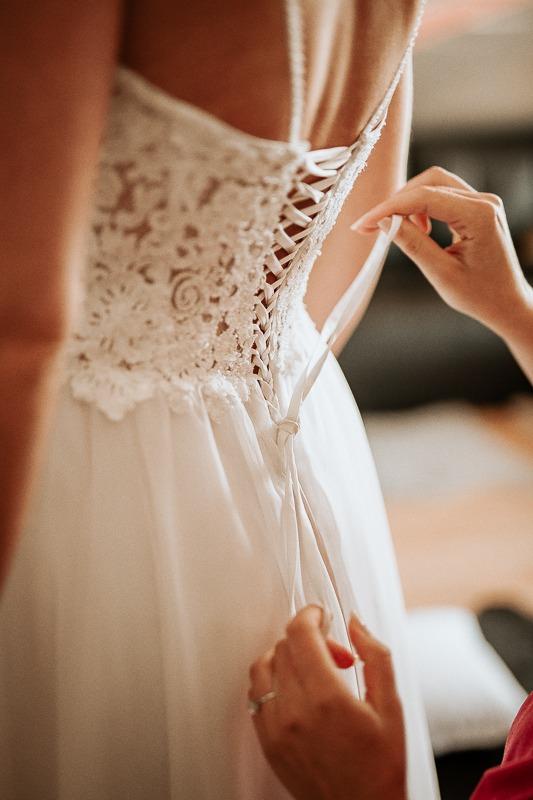 Zawiązywanie gorsetu sukni ślubnej.