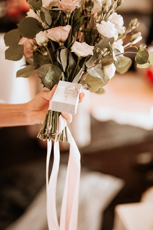 Panna młoda trzyma w ręku kwiaty.