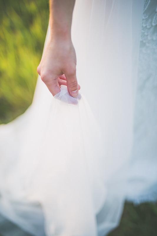 Panna młoda w sukni ślubnej z salonu Arianne trzymająca tren