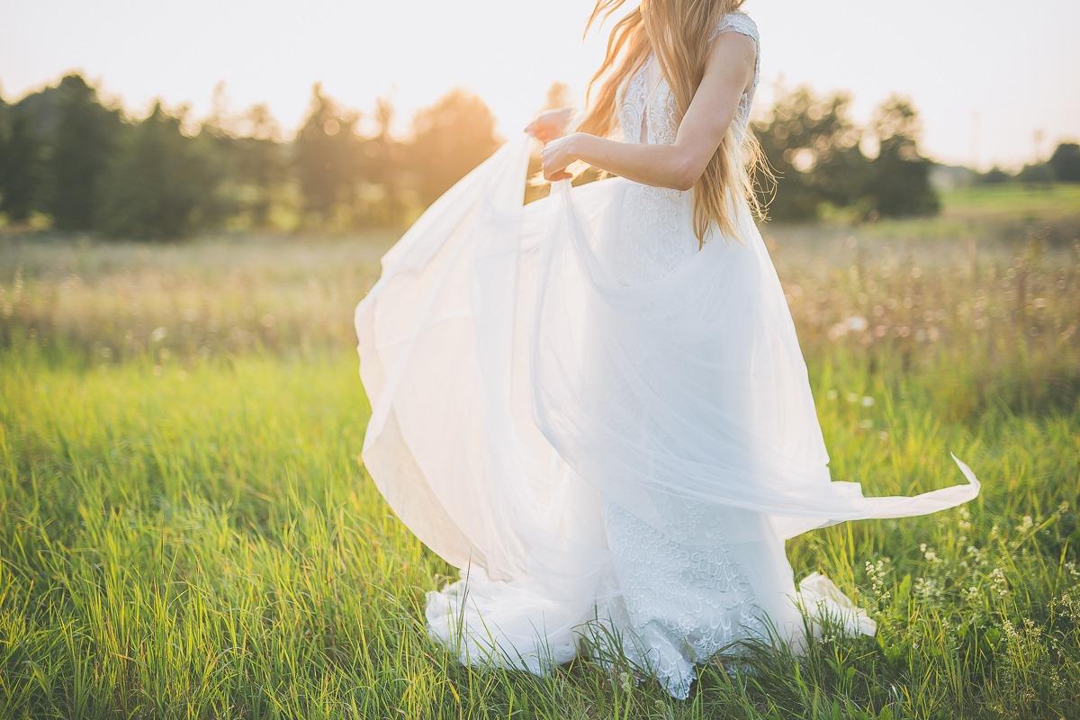 Panna młoda w sukni ślubnej z salonu Arianne machająca trenem