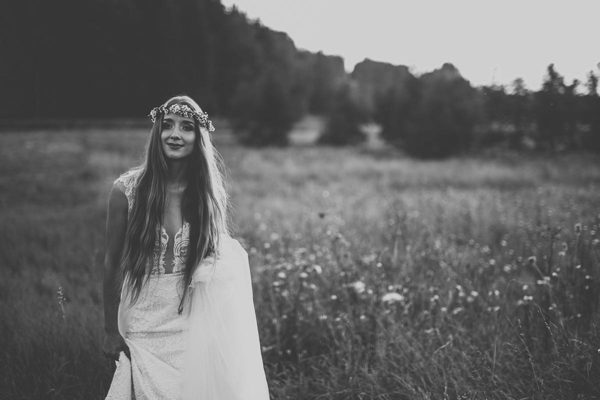 Panna młoda w sukni ślubnej z salonu Arianne idąca na łące