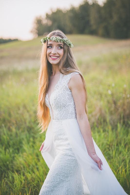 Panna młoda w sukni ślubnej z salonu Arianne uśmiechająca się na łące