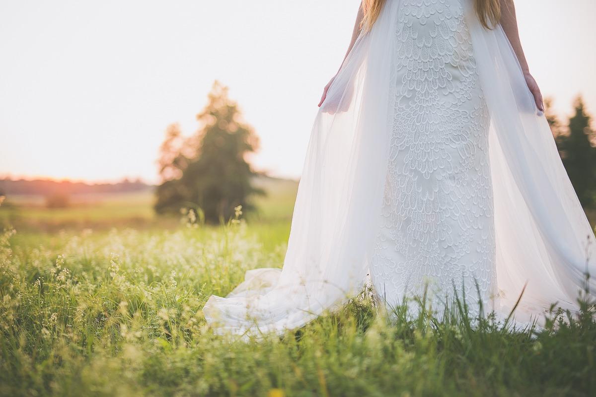 Panna młoda w sukni ślubnej z salonu Arianne stoi na łące