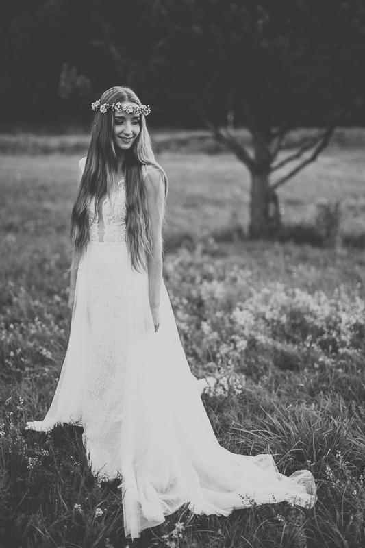Panna młoda w sukni ślubnej z salonu Arianne stojąca na łące