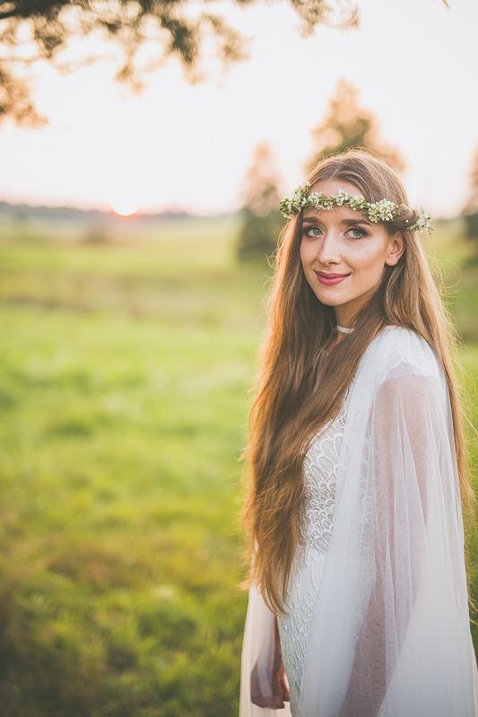 Panna młoda w sukni ślubnej z salonu Arianne stojąca bokiem na łące