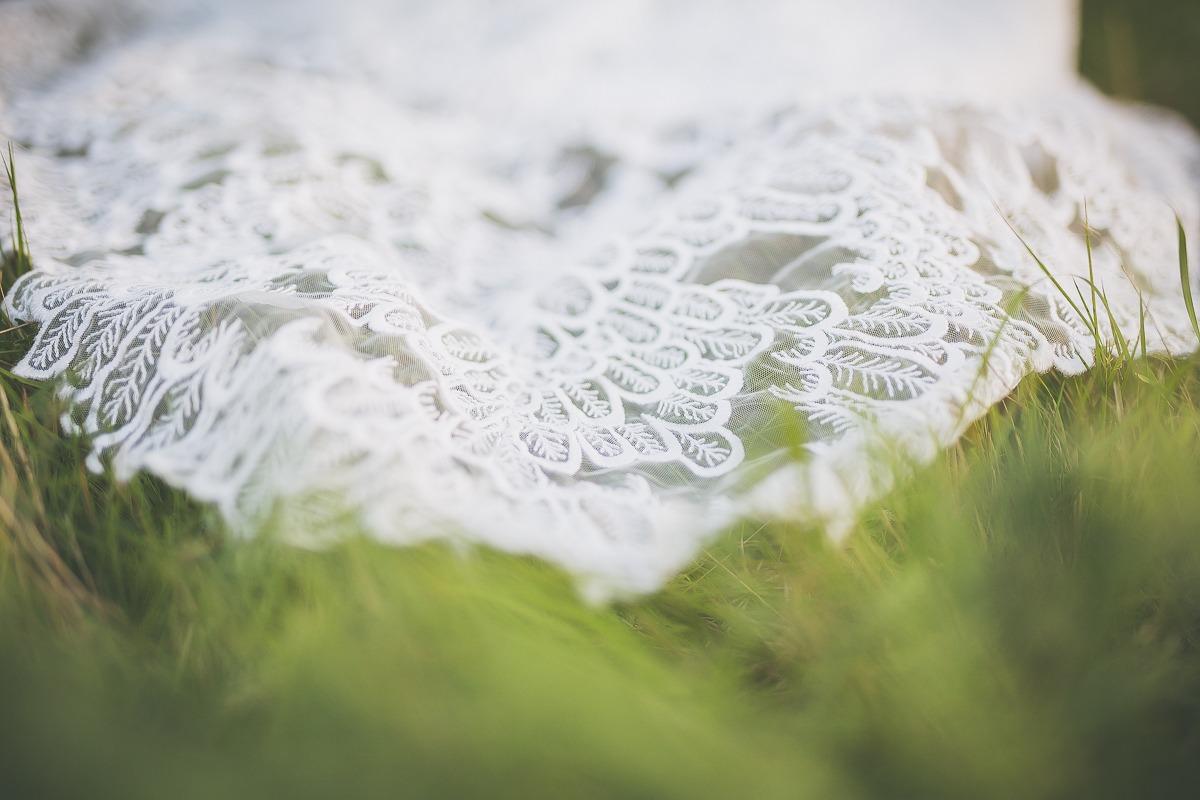 Welon sukni ślubnej ciągnie się po trawie