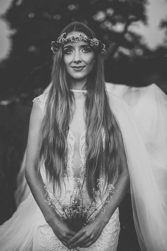 Panna młoda w sukni ślubnej z salonu Arianne w wianku z polnych kwiatów trzymająca bukiet polnych kwiatów od frontu