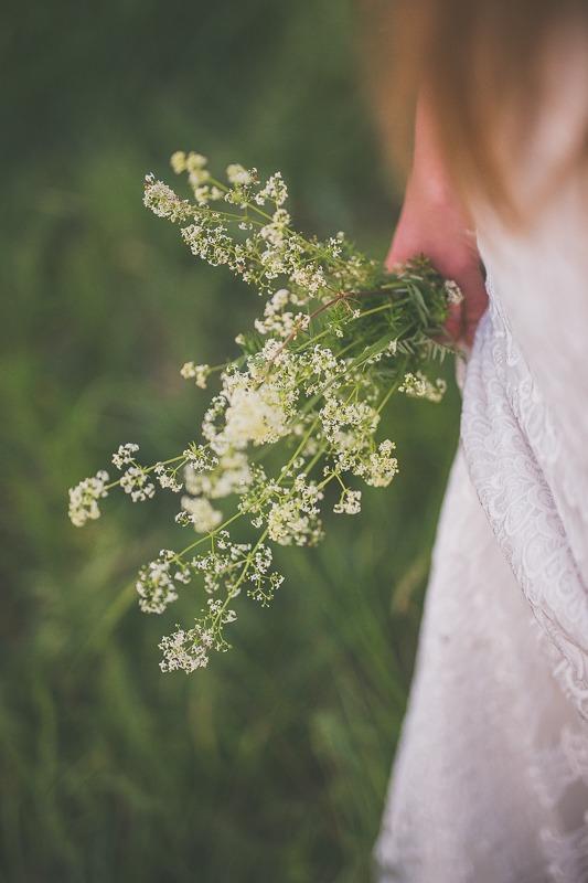 Bukiet polnych kwiatów trzymany przez pannę młodą
