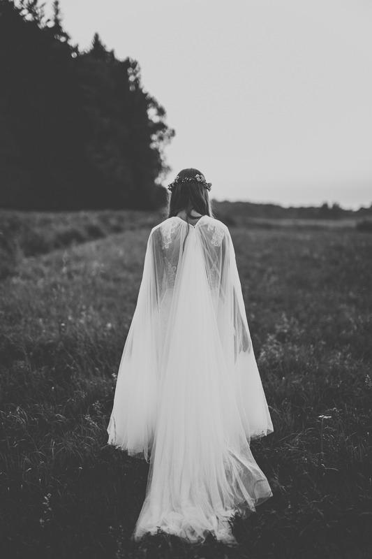 Panna młoda w sukni ślubnej z salonu Arianne w Olsztynie stoi na warmińskiej łące